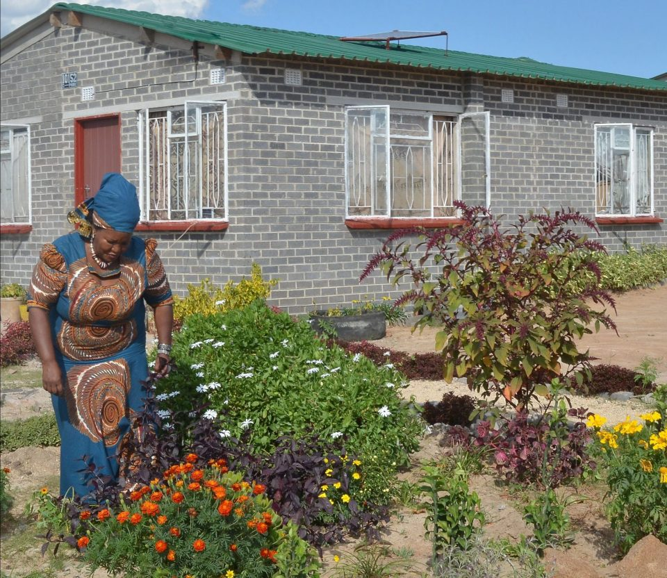 Lady gardening outside her affordable home